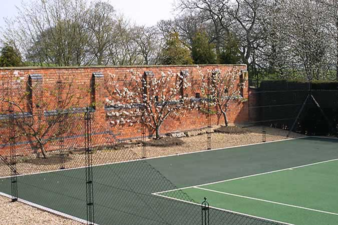 Victorian brick wall frames a tennis court from AMSS tennis court construction