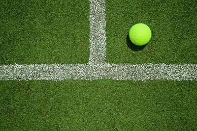 Tennis ball near the line on tennis grass court from top view. Good for background